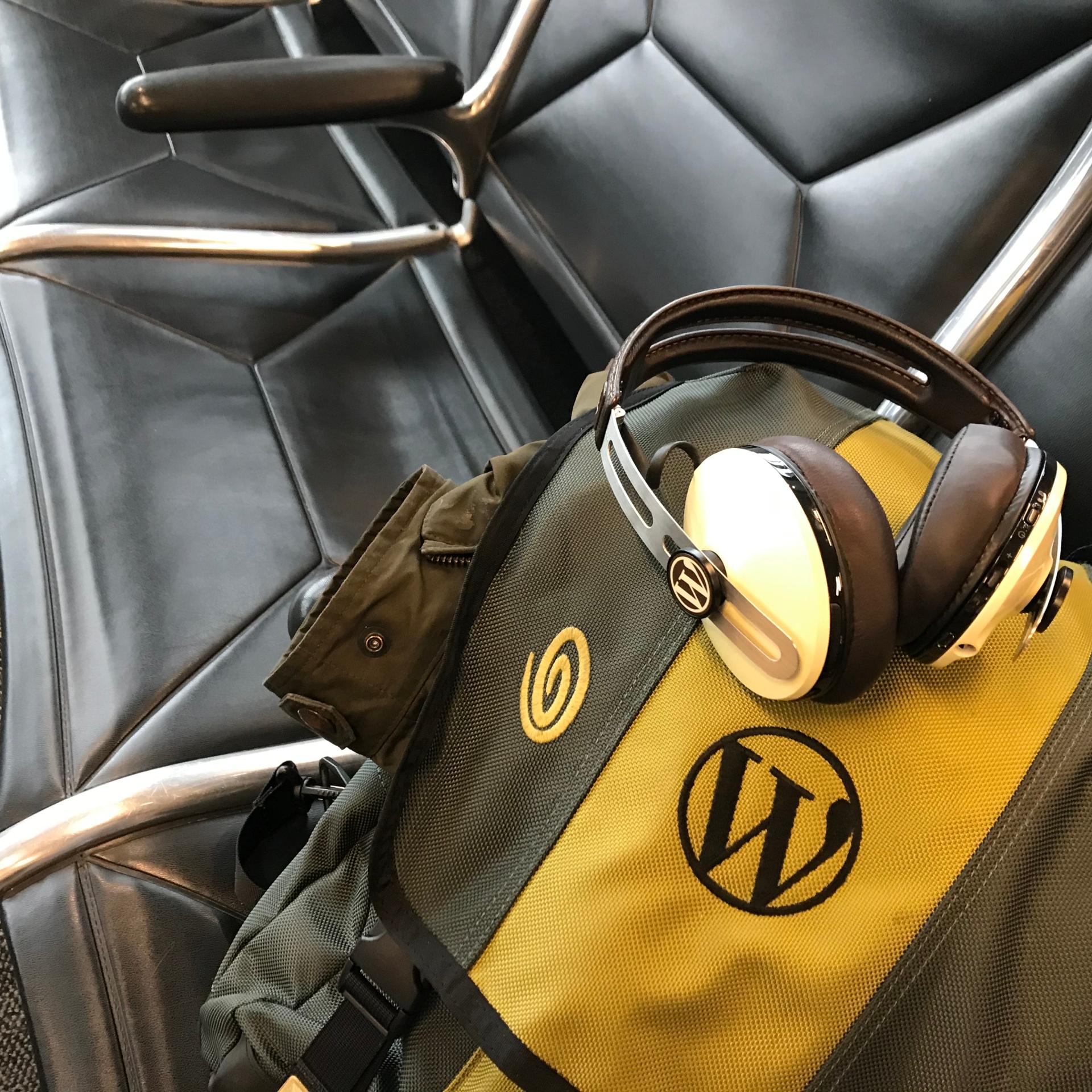 WordPress logos on backpack and headphones in airport